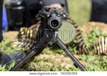 A rifle of mashine gun with ammunition outdoor.