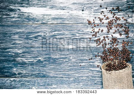 Background of black textured wooden boards with coffee beans scattered of burlap sack. Top view. Copy space