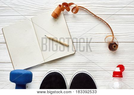 Fitness Concept With Notebook Pencil For Sport Goals And Resolutions, Dumbbells And Sneakers And Wat
