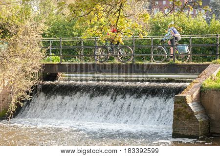 two people cycling on a bridge over a small waterfall