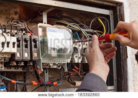 Repair of old electrical switchgear. An electrician replaces old electrical wiring devices