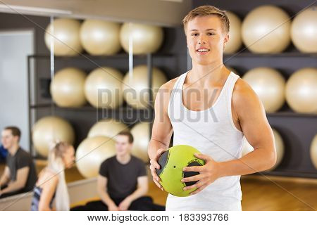 Portrait of smiling young man holding medicine ball while friends resting in gym