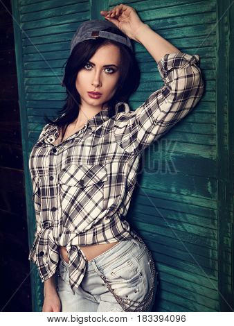 Beautiful Makeup Woman In Trendy Black And White Checkered Shirt And Blue Ripped Jeans Looking Sexy