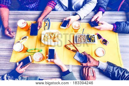 Group of friends texting phone message inside pub top view image - Multicultural teenagers social network addicted together around table with pints of beer and snacks