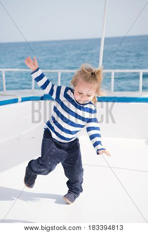 Small Happy Baby Boy Dancing On Yacht In Marine Shirt