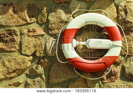 Detailed close up of rescue ring on old brown wall made of stones and rocks.