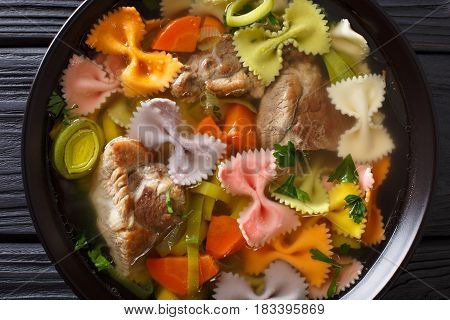 Hearty Meat Soup, With Colored Farfalle Pasta And Vegetables Close-up. Horizontal Top View