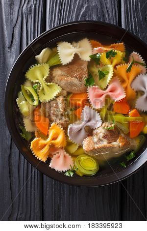 Italian Soup With Pork, Colored Farfalle Pasta And Vegetables Close-up. Vertical Top View