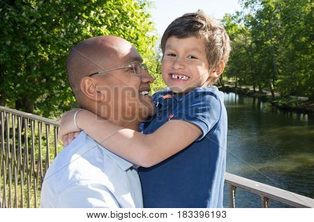 Father And Son Hug On Deck During Summer Vacation