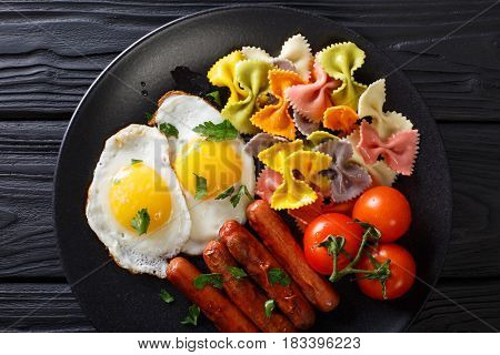 Fried Egg, Sausages, Pasta Farfalle And Tomato Close-up. Horizontal Top View
