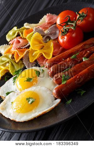 Hearty Breakfast: Fried Eggs, Sausages, Farfalle Pasta And Tomatoes Close-up. Vertical
