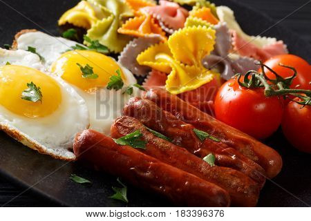 Breakfast: Fried Egg, Sausages, Farfalle Pasta And Tomatoes Close-up. Horizontal