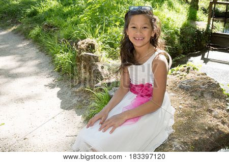 Girl Sitting In The Park With Her White Dress And Big Pink Bow