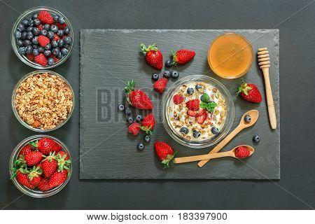 Tasty and healthy breakfast of greek yogurt with berries strawberries, raspberries, blueberries, granola and honey, near ingredients on a black background. Horizontal. Top view.