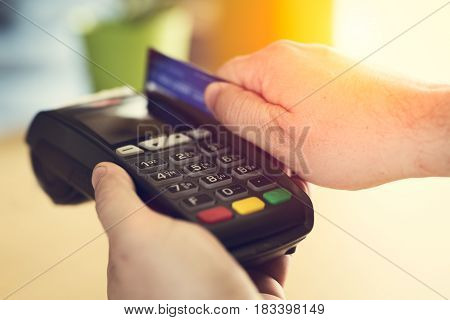 Hand Swiping Credit Card In Store closeup picture