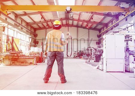 Full length rear view of young manual worker operating crane in factory