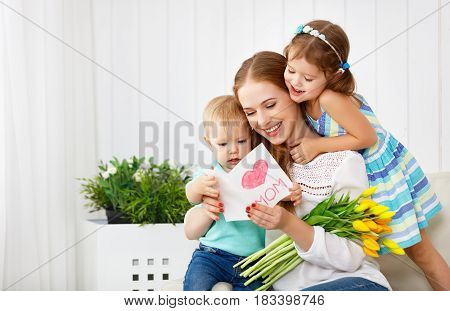 Happy mother's day! Children congratulates moms and gives her a postcard and flowers tulips