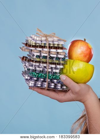 Closeup of human hands holding vitamin tablets pills and fruits. Choice between natural and synthetic vitamins. Health care. Healthy lifestyle nutrition concept.