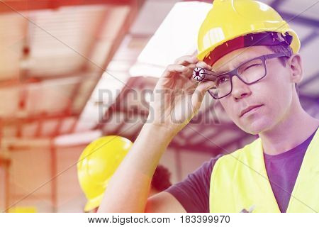 Mid adult manual worker examining metal in industry