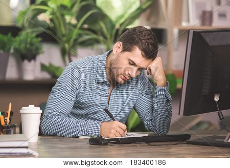 Young man programmer sitting in the office work with computer