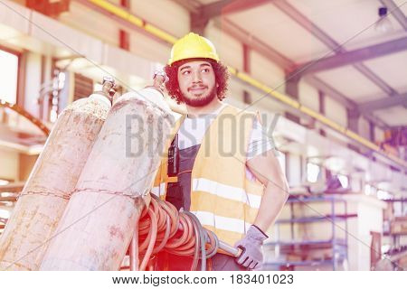 Young manual worker moving gas cylinders in metal industry
