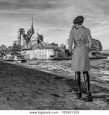 Woman Standing On Embankment Near Notre Dame De Paris