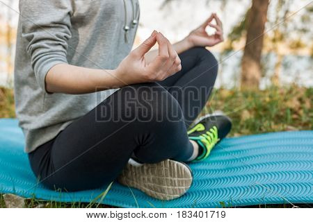 Girl In A Sport Suit, Outdoors, Meditating, Sitting On A Blue Sports Mat