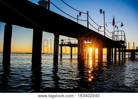 Colourful sea sunrise in soft waves under the pier