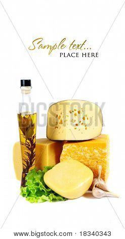 Cheese on a wooden plate and a bottle of olive oil and herbs. Shallow DOF