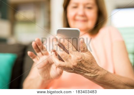 Close up of a pretty mature lady using technology holding her touchscreen phone