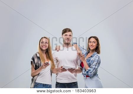 Casual People Group, Young Man Two Woman Happy Smile Using Cell Smart Phone Network Communication Looking To Copy Space Over Grey Background