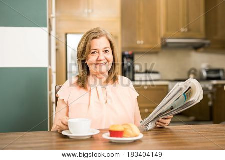 Happy beautiful old woman eating bread and drinking coffee while reading the newspaper alone at home