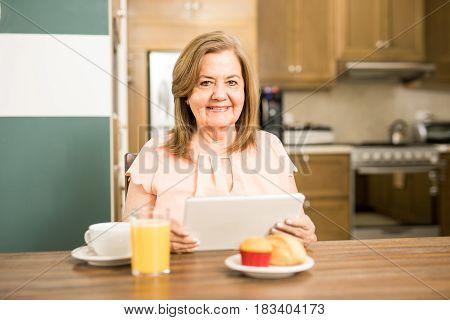 Senior Adult Having Breakfast Holding A Tablet