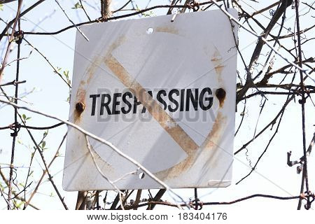 Closeup of old and weathered No trespassing sign posted to wire fence safety concept