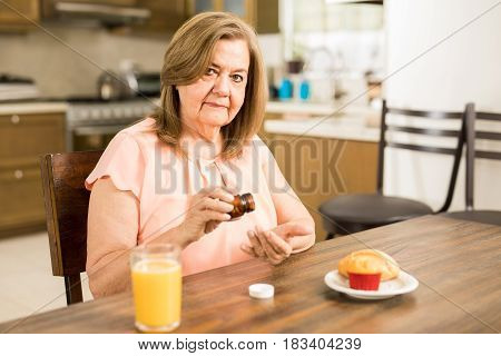 Retired Woman Taking Some Pills In The Morning