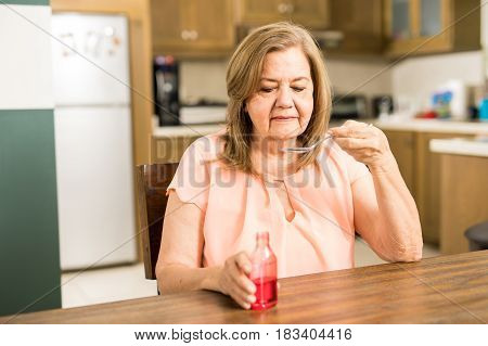 Retired Woman Drinking A Spoon Of Cough Syrup