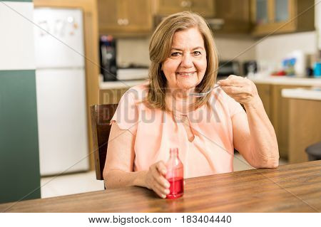 Senior Woman Taking Some Cough Syrup
