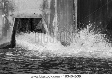 Water splashing and pouring out from a dam overflow concrete culvert black and white image with frozen motion