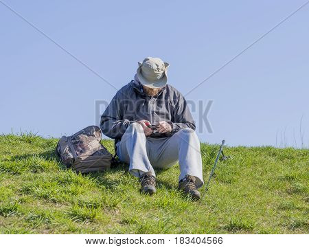 Fisherman sitting on grassy bank cutting fishing line and preparing his gear to catch fish sunny outdoor scene