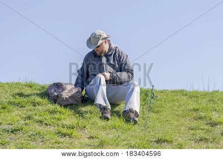 Man getting ready to fish from a grassy riverbank sitting and looking through his gear outdoor activity scene