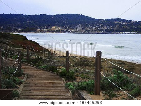 Wooden pathway leading down beach with Monterey, California in the distance