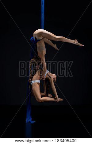 Two slim girls exercising on blue aerial silks in pair studio shot