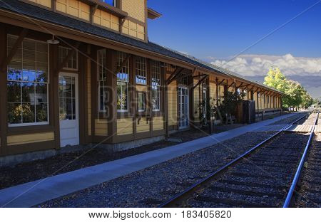 Train station along side train track with blue sky and low clouds in the distance