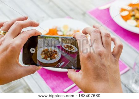 taking a picture of food on table