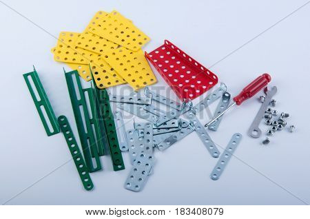 Screw driver nuts wrench bolts and parts of children's metallic constructor lay on white background