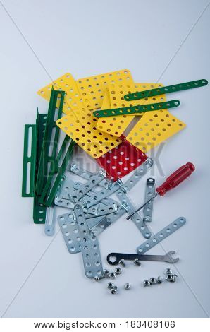 variety of different metallic constructor details and tools laying on white background