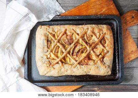 Fresh baked apple pie on the natural wood background top view