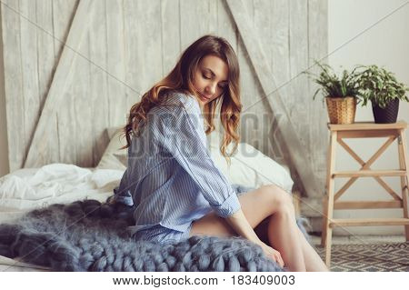 young woman in pajama wake up in the morning in cozy scandinavian bedroom and sitting on bed with houseplants on background. Casual lifestyle in modern interior