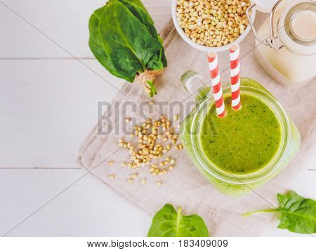 Top view of green smoothie in mason jar on white table. Fresh green smoothie with green buckwheat, spinach and vegan milk. Copy space. Vertical.