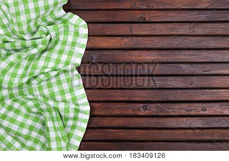 Green checkered tablecloth on dark wooden table with, top view with copy space